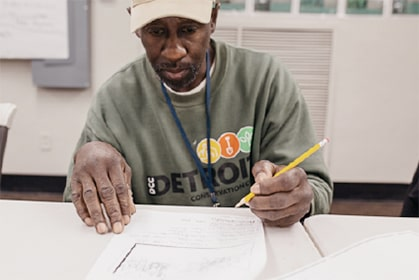 Gile Davis, Detroit Conservation Corps trainee, studying to achieve his certification in the Tree Artisan Program.